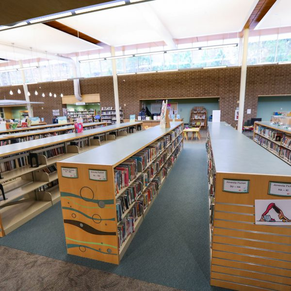 """Tall open space with lots of low bookshelves. The closest ones have signs saying """"Juvenile Fiction"""""""