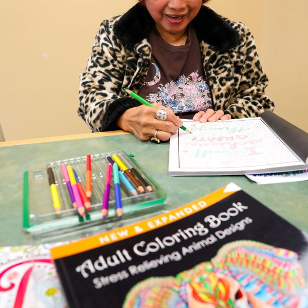 A woman uses colored pencils to work on an adult coloring book