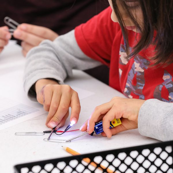 A teen connects a circuit to light up an LED