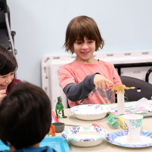 Kids gathered around a table for a craft featuring dinosaur figurines