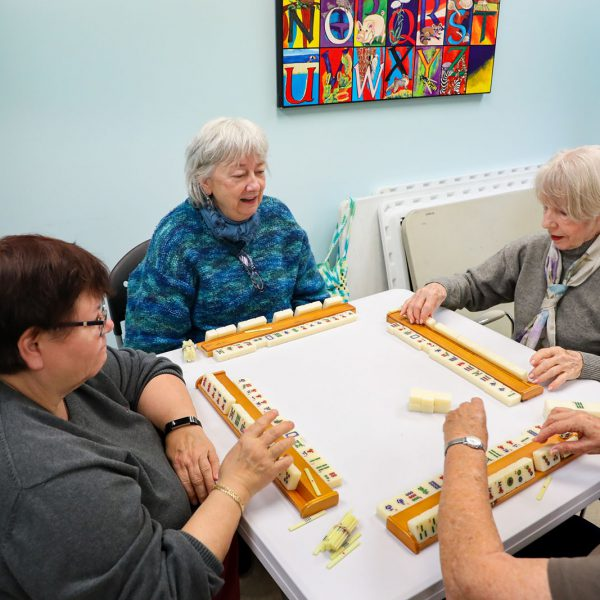 A group of women sitting around a table playing mahjong