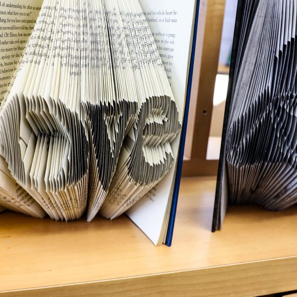 """Book art, with pages folded to make the shape of the word """"Love"""""""