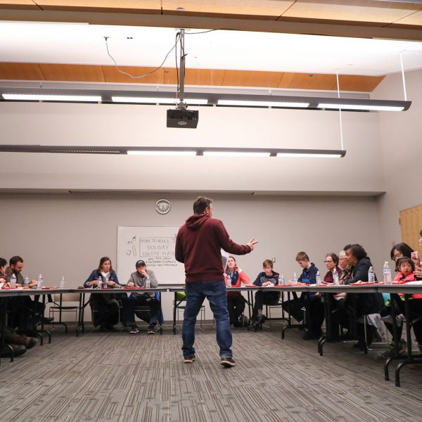 A man stands and speaks to a gathering of people seated around tables.