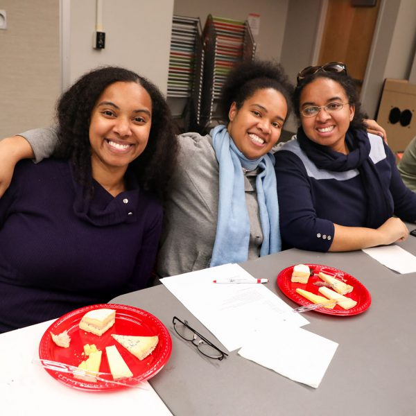 A group of young women smile, each sitting in front of a plate of cheese