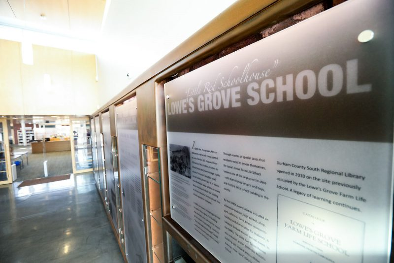 """Display titled """"Little Red Schoolhouse: Lowe's Grove School,"""" with longer text underneath. Other similar signs line the rest of the wall"""