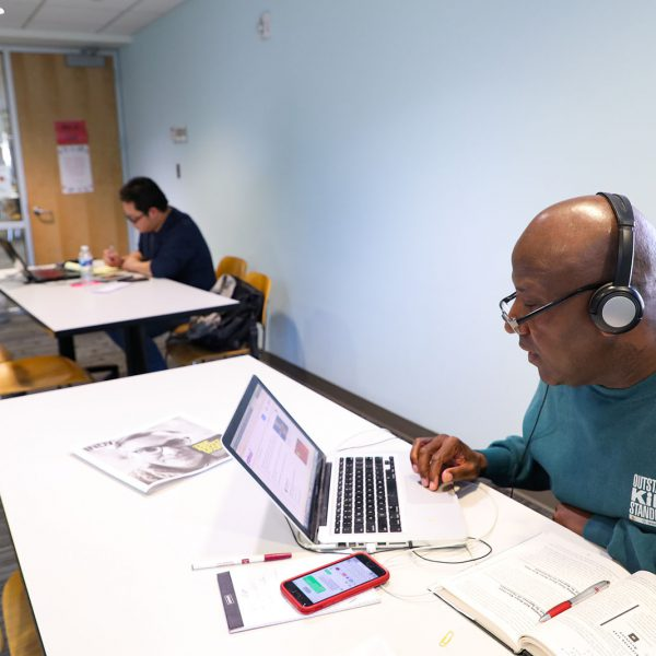 Two people each sit at tables and work on laptops, with phones, open books, and other materials spread out near them