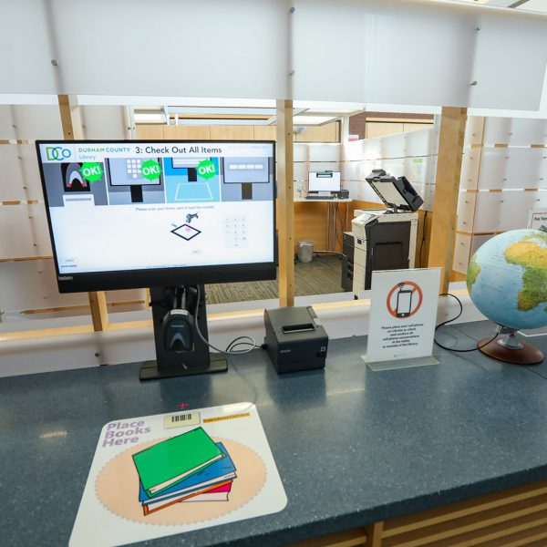 """A self-check machine on a counter, with a pad saying """"place books here"""" and instructions showing on a screen. Past the counter is an area with a copier and another screen"""