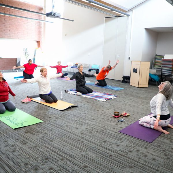 Yoga class with a group of people kneeling on mats and stretching in a large room
