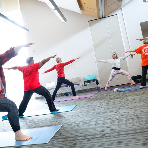 Yoga class with people standing on mats in warrior 2 pose