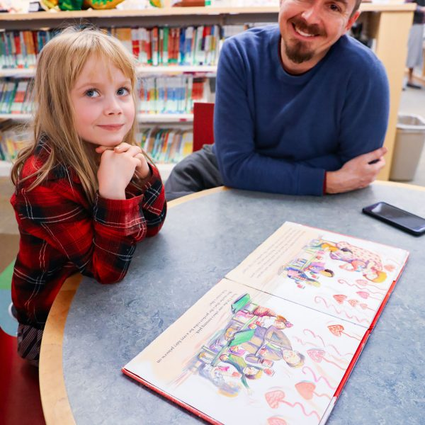 A man and child sit at a table with an open picture book