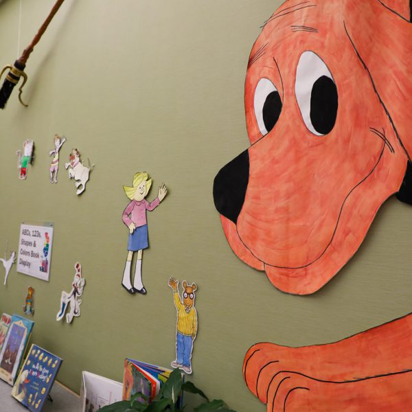 A wall with cutouts of Clifford, Arthur, and other children's book characters