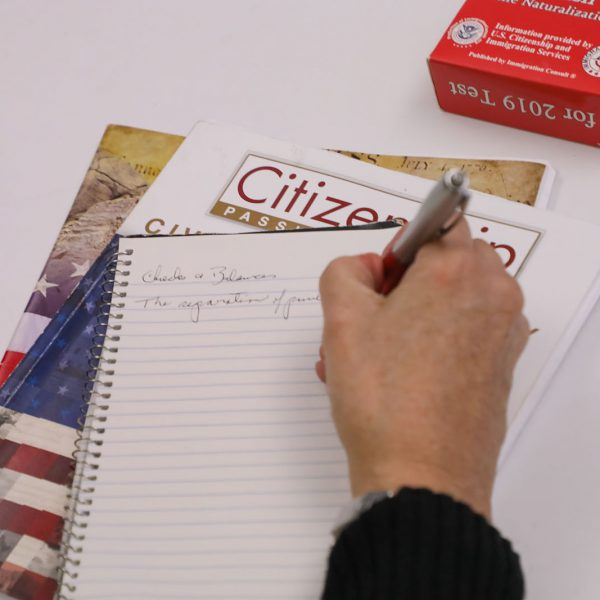 """A hand writing in a notebook on top of a book titled """"Citizenship: Passing the Test"""""""
