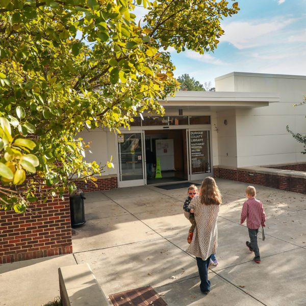 A mother and two small children walk toward the entrance of Southwest Regional Library