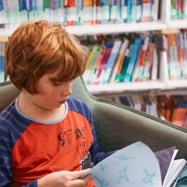 A child sits in a chair and reads a book