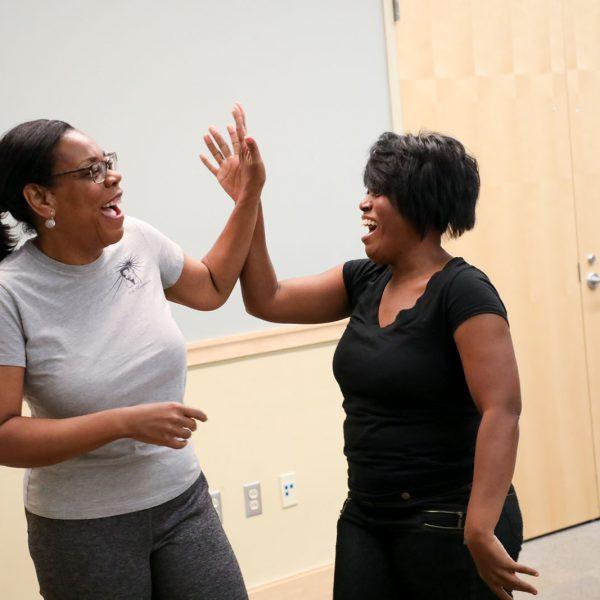 Two women exchange a high five