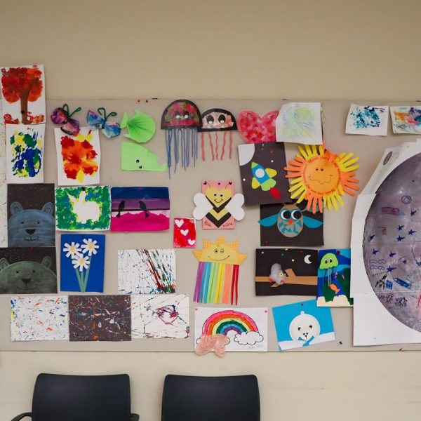 A board full of colorful drawing, paintings, and other arts and crafts
