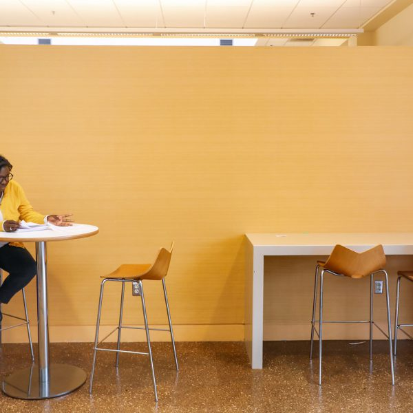 A person sits at a small table with tall chairs, with more chairs at a counter nearby, and looks at a stack of papers