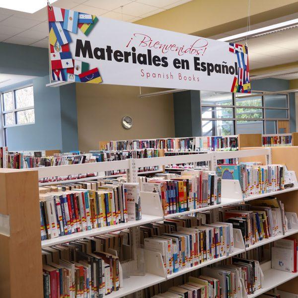 "Bookshelves with sign saying ""¡Bienvenidos! Materiales en Españoll / Spanish Books"" overhead"
