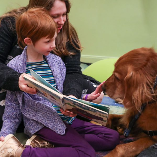 A child pets a visiting therapy dog as her mother holds up a book for them to see