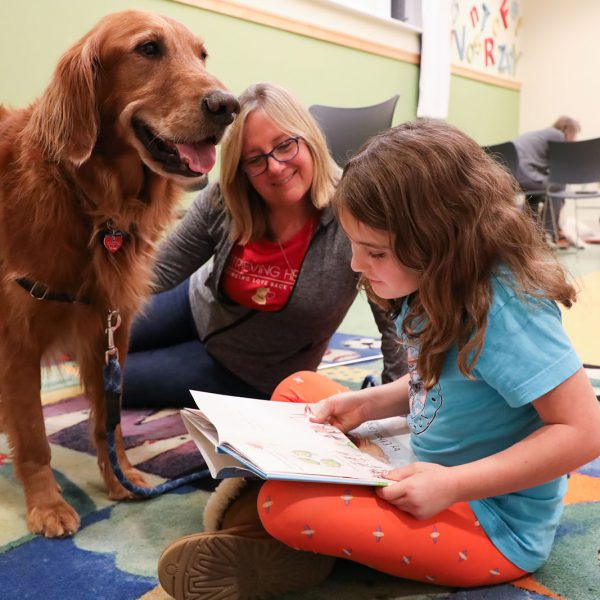 A child reads a book to a visiting therapy dog as an adult looks on