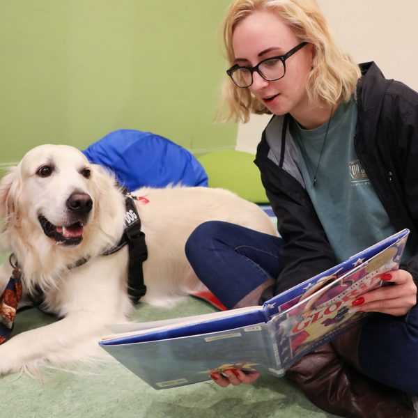 A teen reads a book to a visiting therapy dog