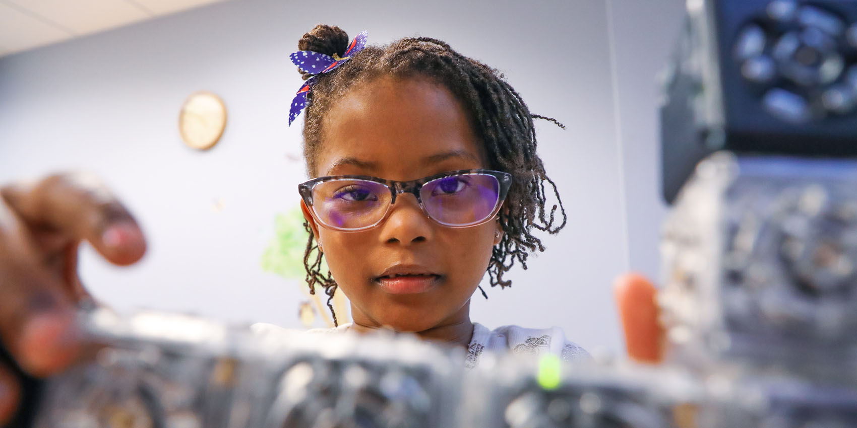 A child looks out from behind a structure she's building with modular robotic blocks