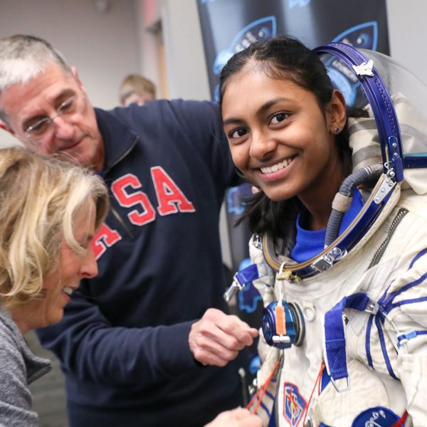 A teen tries on a real astronaut space suit