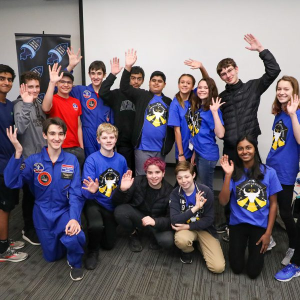 A group of teens, one wearing a flight suit, wave to the camera