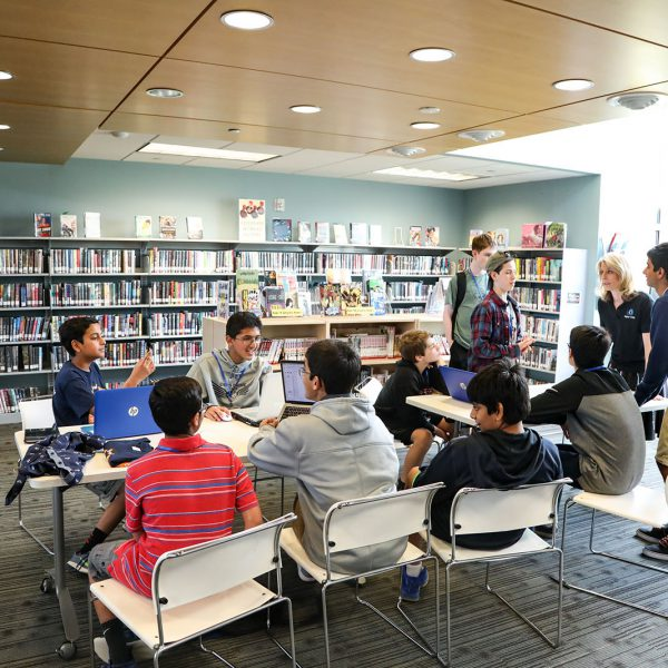 Groups of teens cluster around laptops at a set of tables. Book-filled shelves line the walls behind them