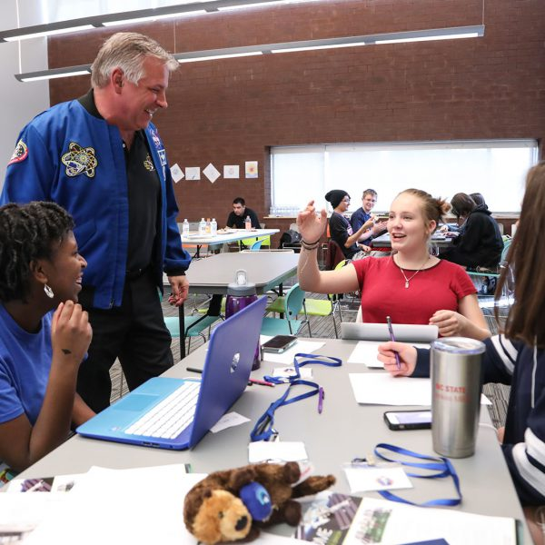 A man in a NASA jacket stands and talks to three teens working at a table