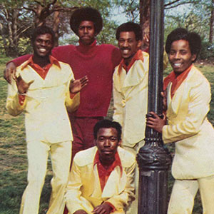 Group photograph of a band with matching outfits