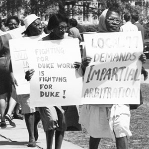 Photograph of employees, students, and faculty protesting in front of the Duke Administration Building