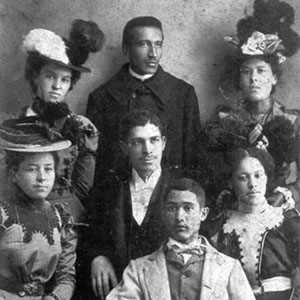 Formal group portrait of young Black men and women in dressy clothes. ca. 1900.