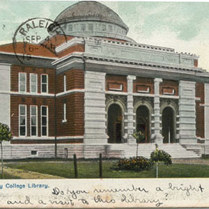 """Postcard with a picture of Trinity College Library, postmarked Raleigh. Handwritten text along the bottom reads, """"Do you remember a bright [day] and a visit to this library?"""""""