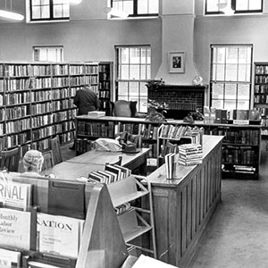 Black-and-white library interior, with bookshelves, windows, and staff working