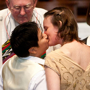 A queer couple kiss at their wedding