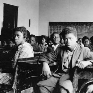 Black children seated at desks in a classroom with chalkboards lining the walls. Photo courtesy of Fisk University Franklin Library, Special Collections