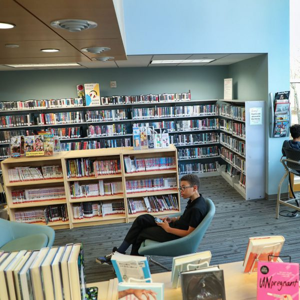 Area with bookshelves, seating, and windows. A teen sits in a chair in the center and looks at his phone